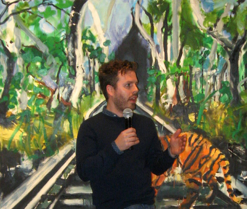 "Luke Gorder gives his artist's talk at Friday night's opening reception. He stands in front of his painting ""Mirage,"" 2015, oil on canvas."