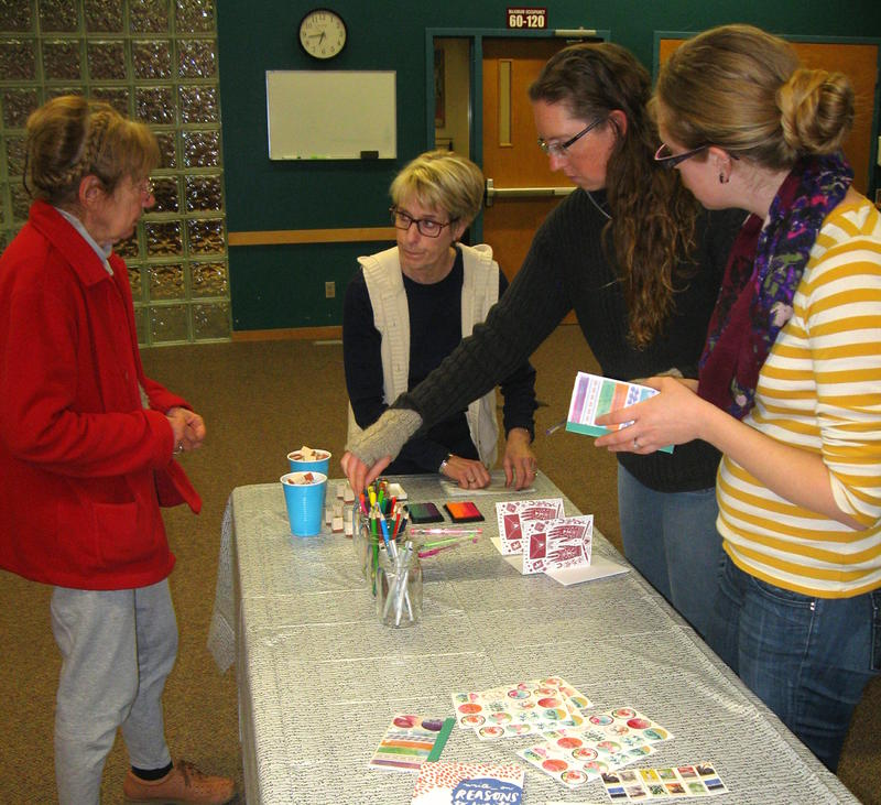 Donna Robinson stands at the head of a table holding stationery, stickers, and stamps at the Write-On kick-off at the library.