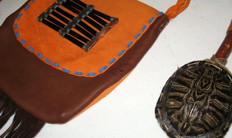 A beaded and fringed leather bag and turtle-shell rattle made by Stan Goodshield Hawkins.