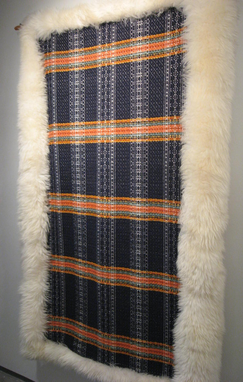This Icelandic Smolandsvav Sleigh Blanket, made of wool, cotton, and sheepskin, is an example of Terry Slagel's weaving. It hangs on the wall at The Dahl as part of the exhibit.