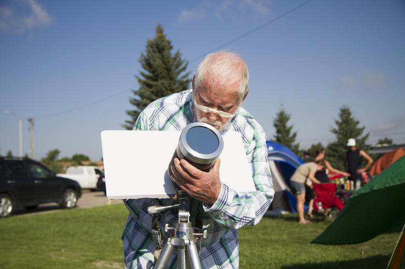 Joe Canfeild from Texas sets up a film camera with a solar filter.