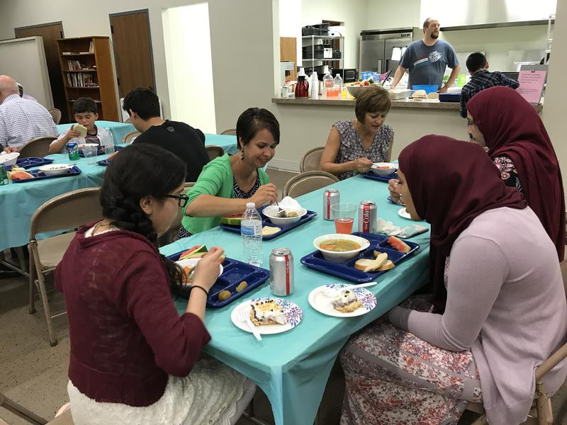 Pastor Amy Martinell (green sweater) dines with members of the Muslim and Lutheran community at Augustana Lutheran Church in Sioux Falls