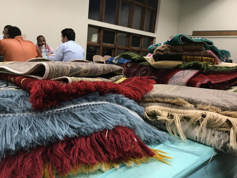 Prayer rugs are stacked as Lutherans and Muslims dine together at Augustana Lutheran Church in Sioux Falls