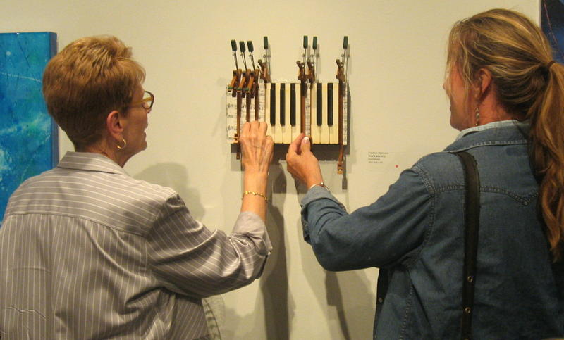 "Carol Hilgemann, left, discusses her assemblage ""Heart and Soul"" with an art patron."