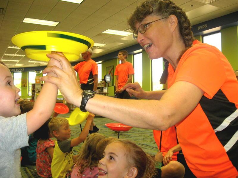 Christa Hanson (the Mom) helps children spin plates.