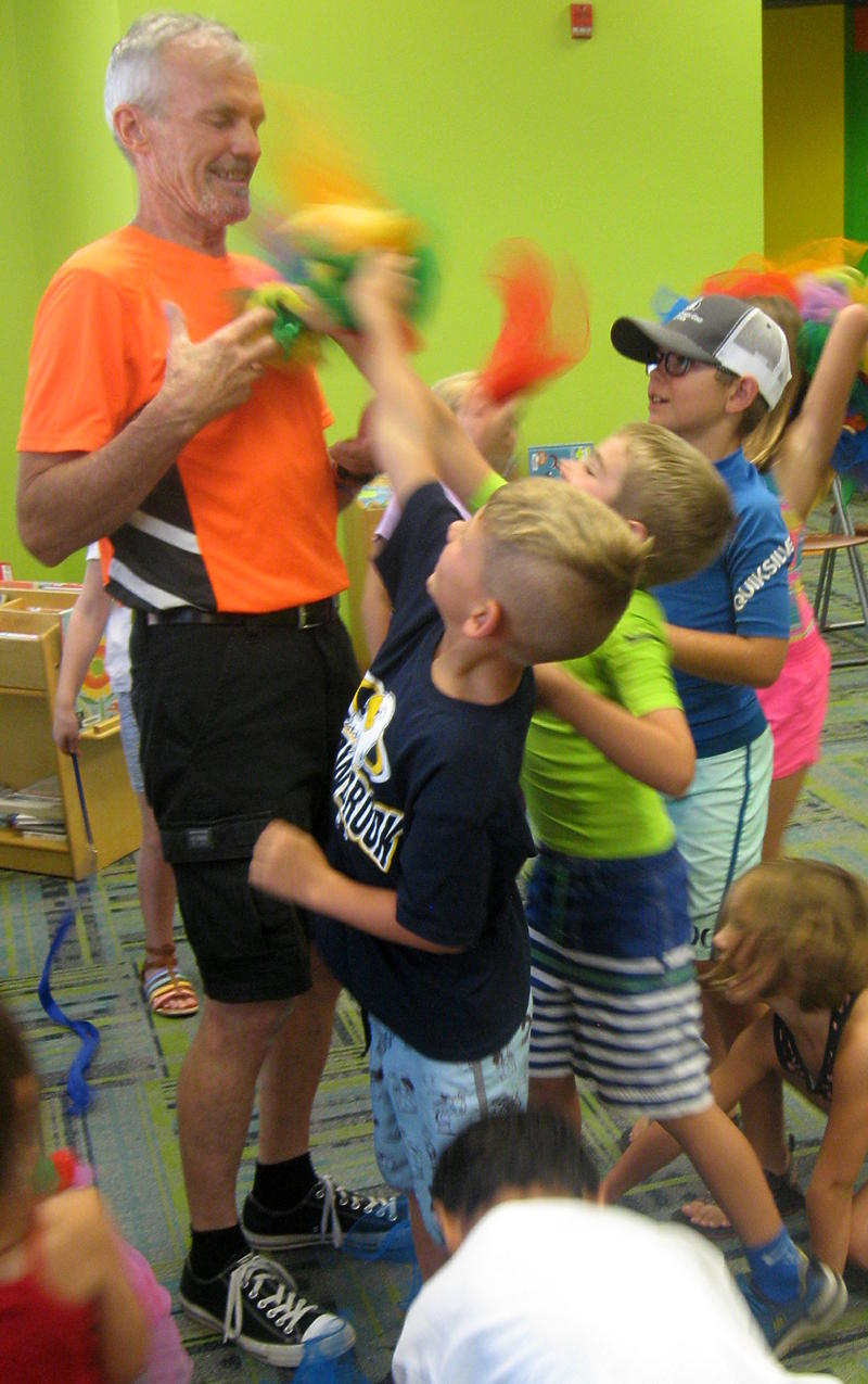 Mark Hanson is attacked by children with scarves. Hanson used the scarves after the show to teach kids how to juggle.
