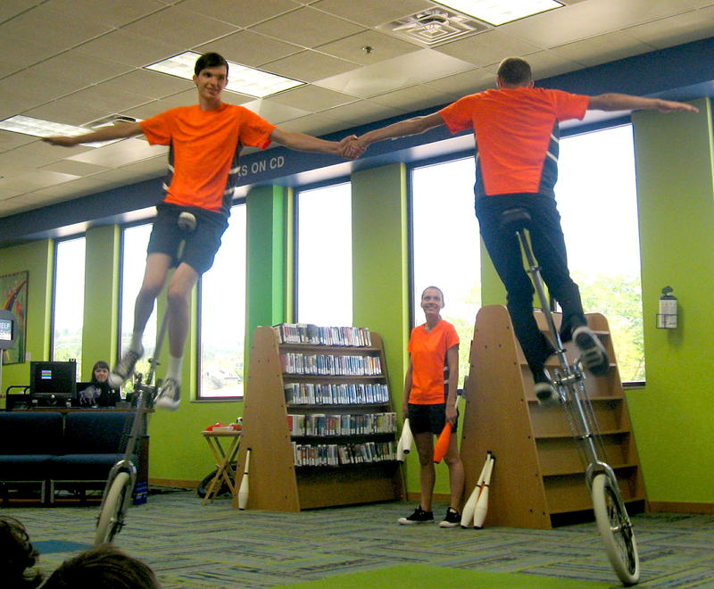 Matthew (L) and Luke Hanson ride tall unicycles while their sister Christa watches.