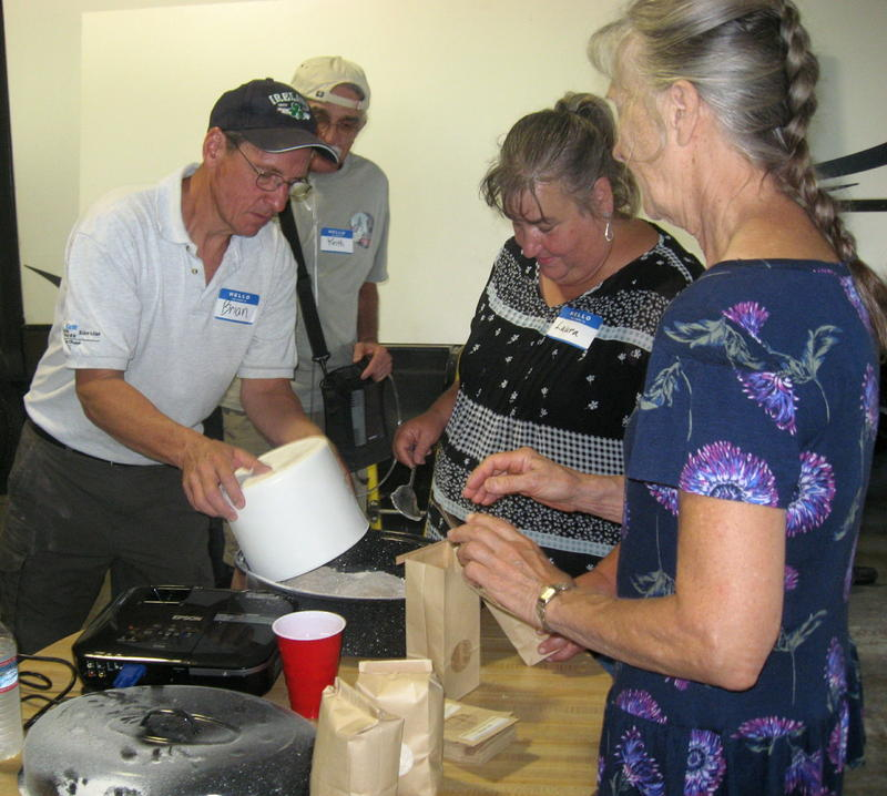 Brian Stambaugh, left, gets a little help from his friends while grinding and bagging red fife flour.