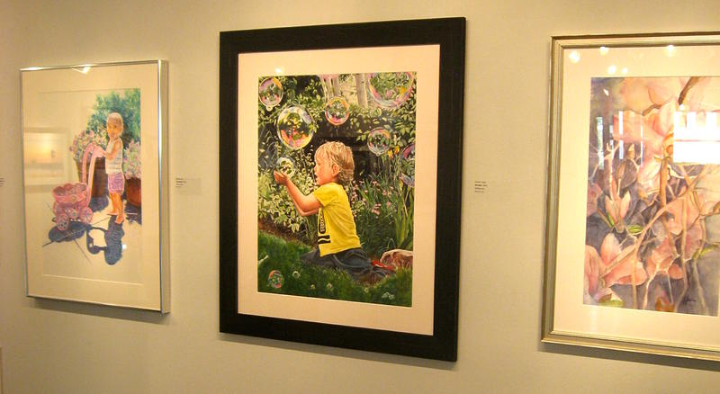 "The center painting, titled ""Wonder,"" by Sharon Grey, received the platinum award."