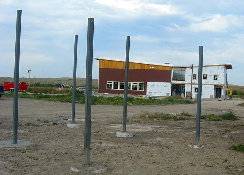 In foreground are posts for a carport. All houses have them. In bg is the community center, with gathering space and bunks for guests.