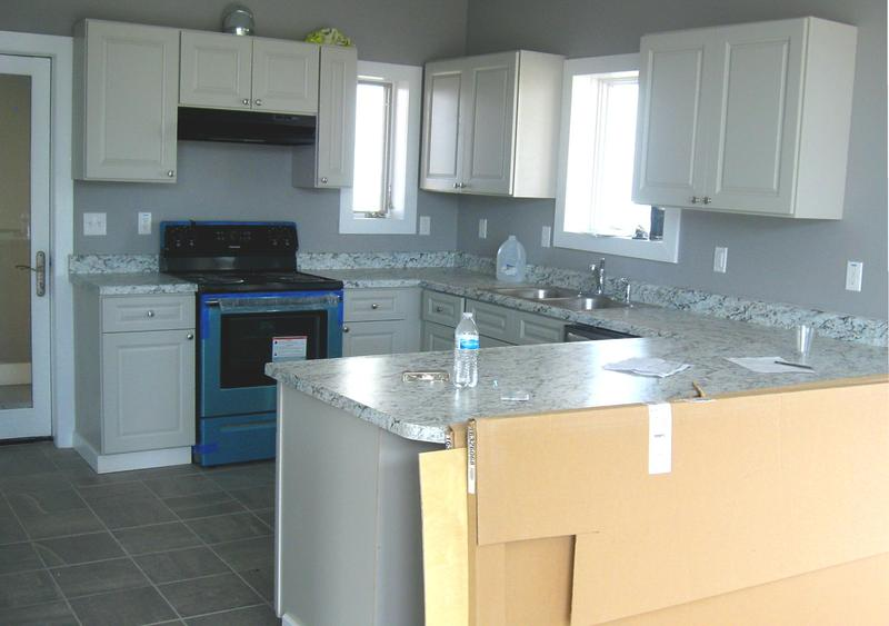 The kitchen of one of the finished houses. The new appliances still have protective blue film.