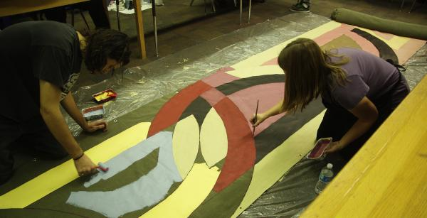 Art teacher Gabrielle Seeley and Ty Stilwell - one of her students -combine their talents to work on a project.