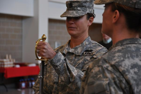 Susan Shoe (left) accepts sword of command during ceremony appointing her as State Command Sergeant Major for South Dakota Army National Guard. Master Sergeant Jen Litzen (right) is the sword bearer.