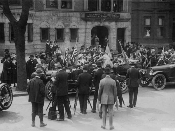 A crowd gathers around the car that will take Jeanette Rankin, the first female member of Congress, to be sworn in in 1917.