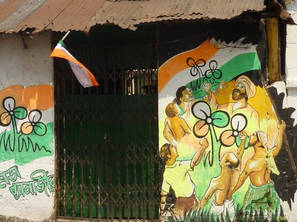 A house on a small side street in Calcutta is adorned with election graffiti. The Trinamool Congress logo looks like a three-leaf clover.  The name of that party's candidate, Mamata Banerjee, is written in Bengali on the lower left.
