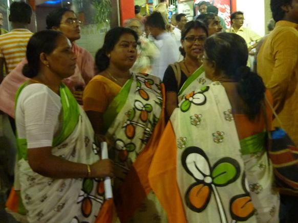 Supporters of Mamata Banerjee rally in Calcutta wearing the Trinamool party colors and logo. The three leaf clover-like symbol represents leaves of grass and grass flowers - to suggest a grassroots party.
