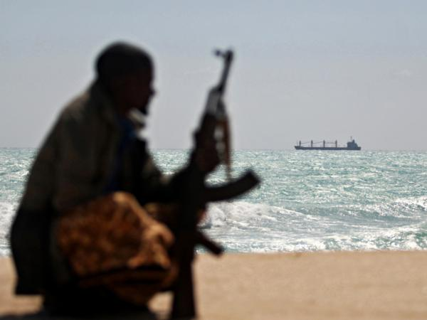 An armed Somali pirate along the coastline with Greek cargo ship, MV Filitsa, is seen anchored just off the shores of Hobyo town in northeastern Somalia where its being held by pirates.