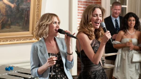 Kristen Wiig (left) breaks the tired mold of summer wedding comedies with <em>Bridesmaids</em>, where her character grapples with a rival (Rose Bryne) without the genre's typically inconceivable levels of earnestness.