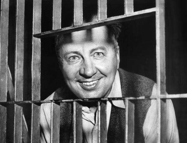 "George Metesky, who confessed to being the ""Mad Bomber,"" looks through the bars of his cell at the Waterbury, Conn., Police Station."