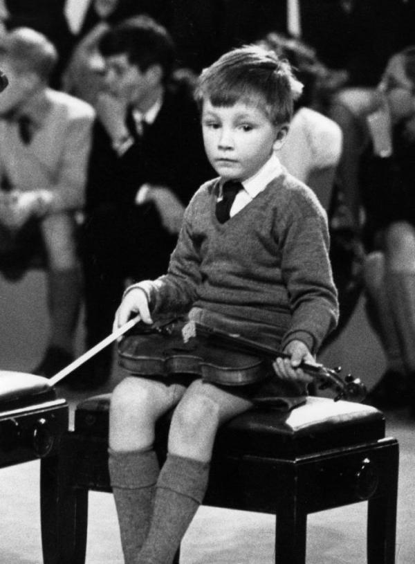 This lad looks less than enthused about classical music. (Actually, it's a very young Nigel Kennedy, captured by a cameraman in 1964.)