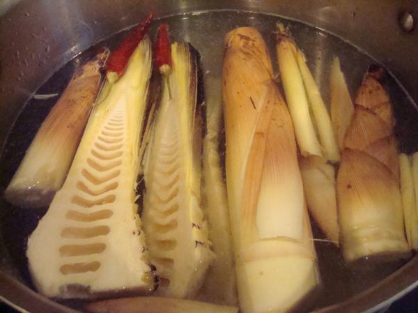 The fresh bamboo shoots are boiled in water with rice bran flour to neutralize toxins and chilies to add spice and prevent spoilage.
