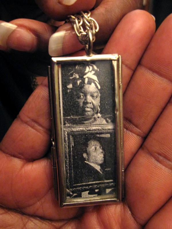 Mary Johnson holds a two-sided locket she wears on a necklace. On one side are photos of herself and her son; the other has a picture of Oshea Israel.