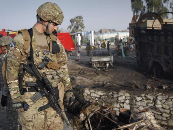 An unidentified U.S. soldier at the scene of a suicide attack in Jalalabad, Nangarhar province in Afghanistan on Wednesday. Rumors have arose that the White House will begin reducing troops in July, a prediction met with criticism.