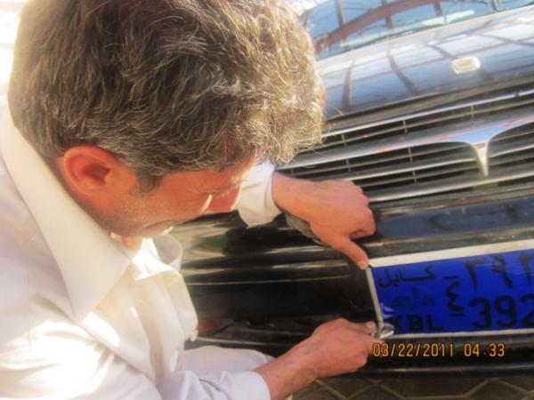 Waseh, an Afghan driver working for an international NGO, is trying to cover the license plate containing the number 39 with a blue plastic sheet. He is also 39 years old.