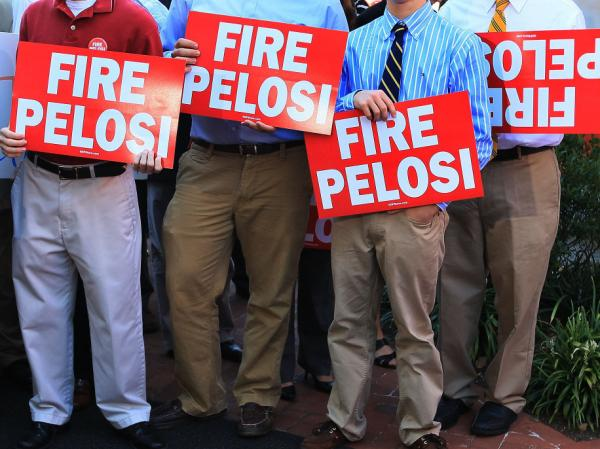"Capitol Hill staffers hold signs while participating in the launching of the RNC-sponsored ""Fire Pelosi"" bus tour last September in Washington. The former House speaker says she doesn't have time to worry about the attacks on her. ""You just have to decide,"" she says. ""Do I care about that, or do I care about getting a job done?"""