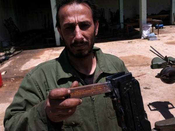"At the rebels' outdoor machine shop, they rehabilitate antique automatic weapons and sometimes redesign them.  Saleh Likhfayfe shows off the new ""grip"" welded onto a salvaged machine gun."