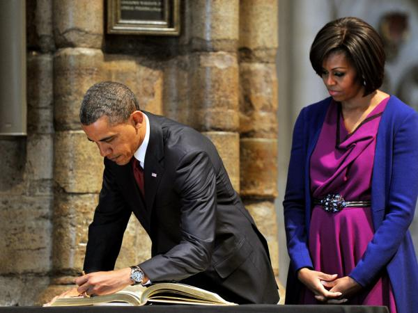 President Obama enters his misdated message in the Westminster guestbook.