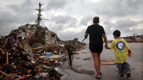Kimmy Lankford and her 5-year-old son, Jack, walk through their neighborhood Wednesday after a massive tornado passed through the town. The Lankfords continue to live in their home a few blocks away, which was damaged but remains habitable.
