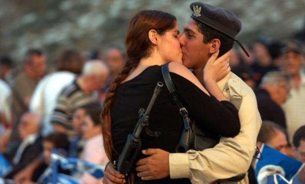 An Israeli Air Force cadet kisses his girlfriend before being sworn in for duty in 2003. A new study that measures the rigidity of a culture's social rules and standards — including when and where it's appropriate to kiss — found Israel to be culturally loose.