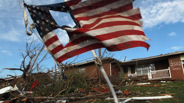 A torn U.S. flag hangs outside of a house damaged during Sunday's massive tornado in Joplin, Mo. As of Thursday, local police said they had arrested 16 people for looting and burglary and four for assault since the twister hit.