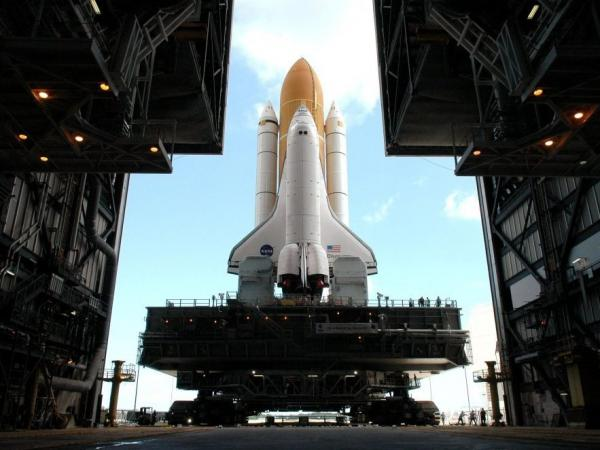 Framed in the doors of the Kennedy Center's Vehicle Assembly Building, the crawler begins the long journey towards Launch Pad 37B with Space Shuttle Discovery in April 2005.  This enormous cross between a tank and a cargo ship is the largest self-powered land vehicle in the world.