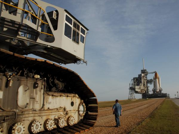 "The crawler's titanic treads grip the dirt of the ""crawlerway,"" a special road between the launch ad and the hangar-like structure where the shuttle is assembled.  The road is designed to hold the combined 18 million pounds of the crawler and the shuttle it carries."