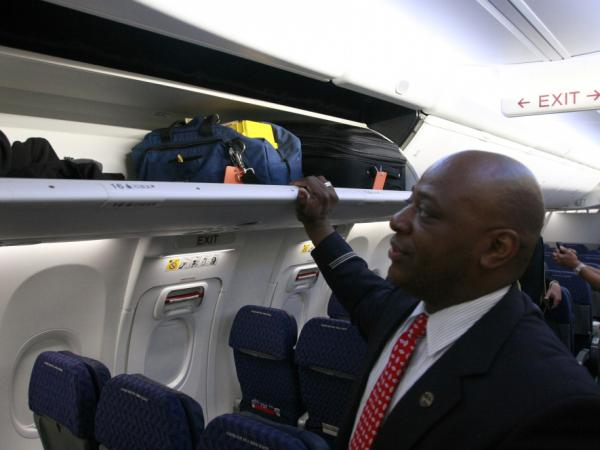 A flight attendant prepares to close a luggage bin on the redesigned 737. Thanks to the bin's new pivoting motion, passengers in the aisle seat will have more headroom.