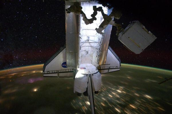 Backdropped by a night time view of the Earth and the starry sky, the Space Shuttle Endeavour is photographed docked at the International Space Station on May 28, 2011. The STS-134 astronauts left the station the next day on May 29, after delivering the Alpha Magnetic Spectrometer and performing four spacewalks during Endeavour's final mission.