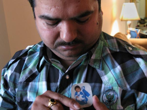 Dinesh Kumar looks down at a portrait of his baby son who died when he was 5-weeks old.