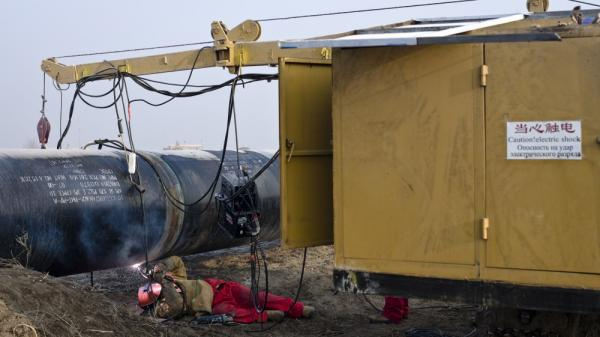 A worker welds at the China-Kazakhstan pipeline junction in Xinjiang, China, in 2008.