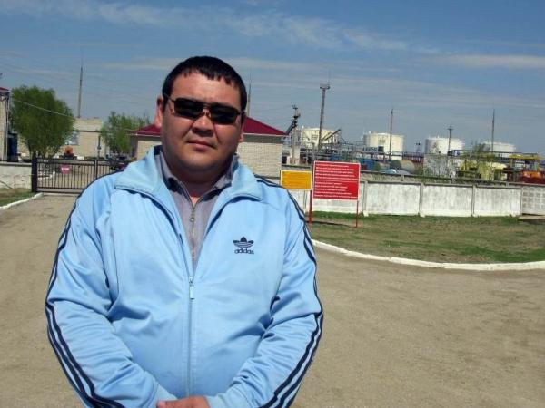 Nurlan Akhmetalin, 38, stands in front of a Chinese-owned oil processing facility near Aktobe, Kazakhstan. Now a cab driver, he worked for the China National Petroleum Corporation from 1996 to 2009. He made good money, but became less comfortable with how Chinese bosses treated employees and suspicious of China's intentions in his country.