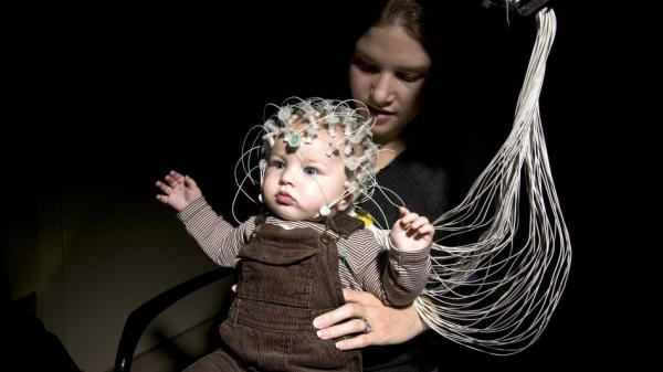An infant and his mother demonstrate electroencephalography, or EEG, technology at Children's Hospital in Boston. The technology could help detect the risk of autism in infants.