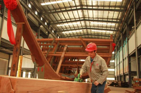 A worker in Nanjing planes a beam for a replica of one of Zheng He's treasure ships, which the explorer sailed in the 1400s.