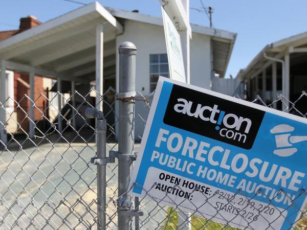 A foreclosure sign hangs on a fence in front of a foreclosed home on April 6 in Richmond, California.