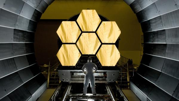 NASA engineer Ernie Wright looks on as the first six primary mirror segments for the James Webb Space Telescope are prepped to begin final cryogenic testing at NASA's Marshall Space Flight Center. The telescope will have 18 primary mirror segments.