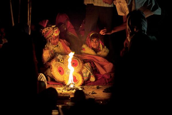 Rajani and her boy groom barely look at each other as they are married in front of the sacred fire. By tradition, the young bride is expected to live at home until puberty, when a second ceremony transfers her to her husband.
