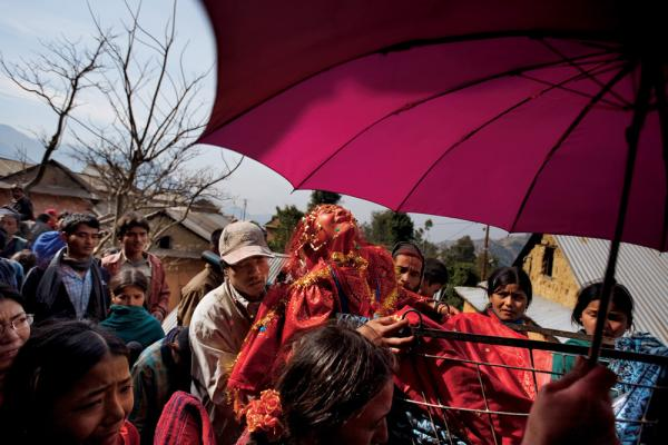Although early marriage is the norm in her small Nepali village, 16-year-old Surita wails in protest as she leaves her family's home, shielded by a traditional wedding umbrella and carried in a cart to her new husband's village.