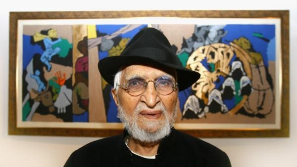M.F Husain in London in 2007. One of his paintings, which depicts Mother Teresa taking care of children, is in the background.