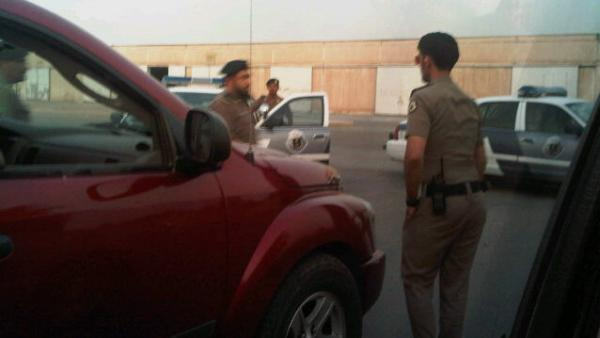 Saudi policemen surrounding the cars of women who drove.