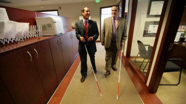 Attorney Richard Bernstein, left, and Angelo Binno walk through the law office of The Bernstein Law Firm in Farmington Hills on May 24, 2011. Binno, 28, of West Bloomfield, is suing the American Bar Association. Binno, who is legally blind, said the ABA standards don't accommodate blind law school applicants.
